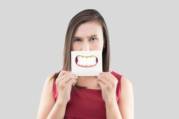 Asian woman in the red shirt holding a brown paper with the dental plaque cartoon picture of his mouth against the gray wall, bad breath or halitosis, the concept with healthcare gums and teeth Premium Photo