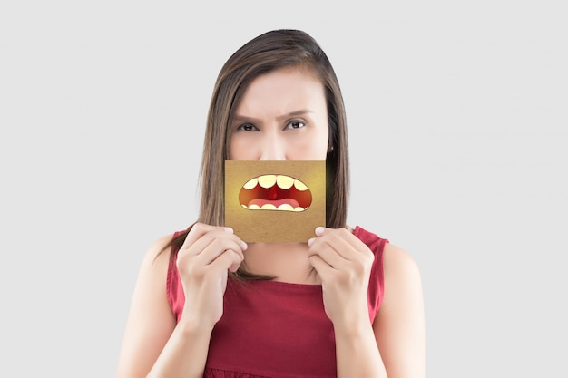 Asian woman in the red shirt holding a brown paper with the yellow teeth cartoon picture of his mouth on gray Premium Photo
