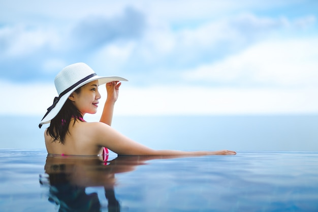 Asian woman relax in pool on beach Premium Photo