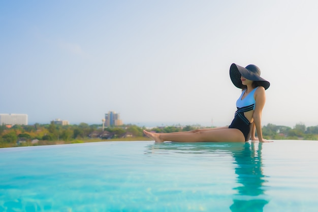 Asian woman relaxing by the swimming pool Free Photo
