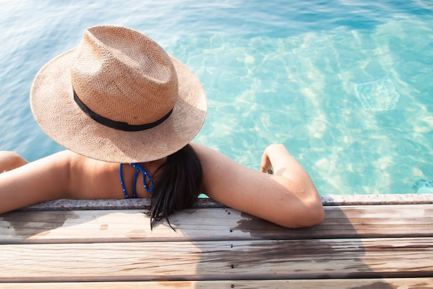 Asian woman relaxing in swimming pool, travel vacation concept Premium Photo