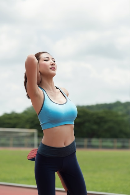 Asian woman runner warm up and exercising in the stadium. Premium Photo
