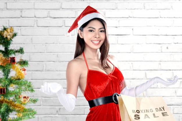 Asian woman in santa costume holding shopping bags with boxing day sale text Premium Photo