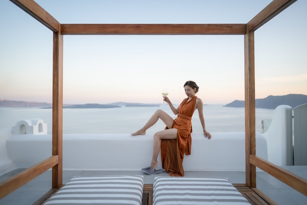 Asian woman in sexy dress witha glass of wine enjoying view oia village in santorini island, greece. Premium Photo