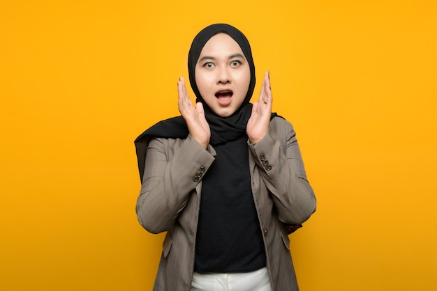 黄色の背景にショックを受けたアジアの女性 Premium写真