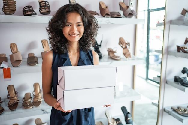 Asian woman shop assistant with shoe boxes at store Premium Photo