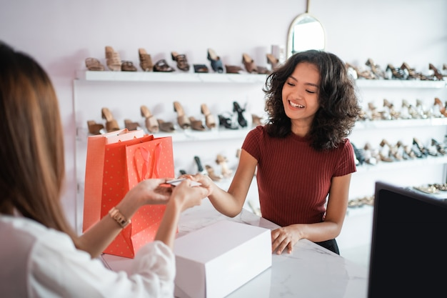 Asian woman shop assistant with shoe boxes at store Premium Photo