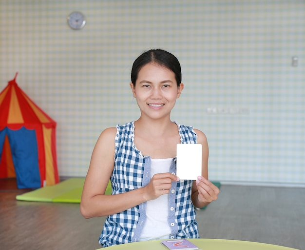 Asian woman show the blank flash card for right brain development at the kid playroom Premium Photo
