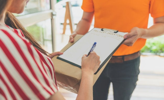 Asian woman signing receiving package box on delivery order form for confirm received complete from delivery man in orange uniform at her home Premium Photo