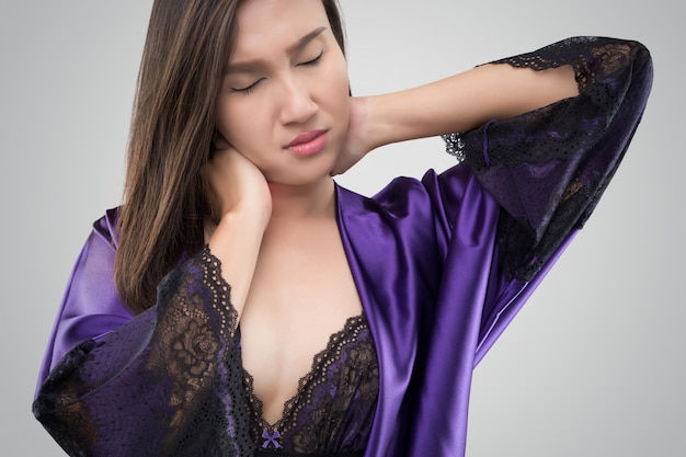 Asian woman in the silk nightwear and purple robe who is having pain in her neck on a gray background Premium Photo