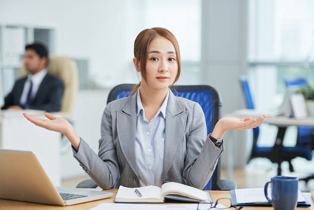 Asian woman sitting at desk in office and looking at camera with helpless hand gesture Free Photo