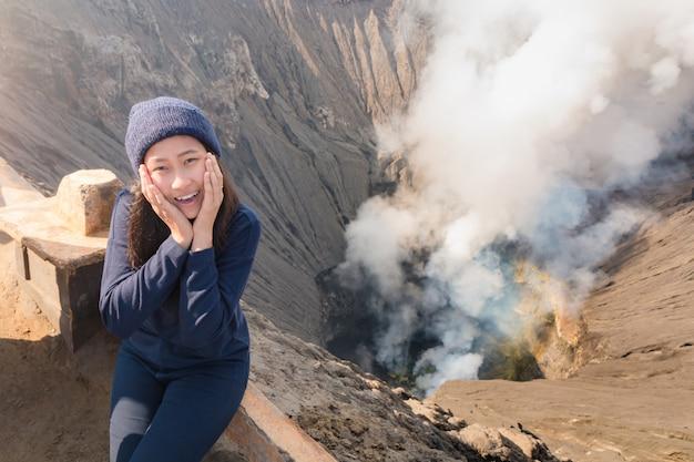 Asian woman sitting near volcano crater with erupting smoke. Premium Photo