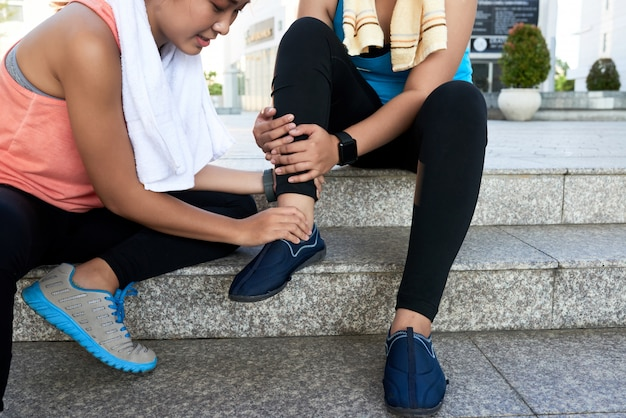 Asian woman sitting on steps in street and holding friend's ankle Free Photo