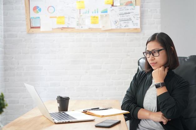 Asian woman sitting in stylish watching interesting training webinar online laptop computer Premium Photo