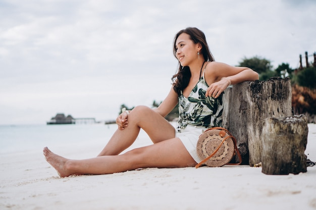 Asian woman sitting on white sand by the indian ocean Free Photo
