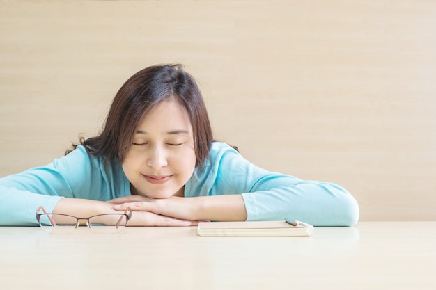 Asian woman sleep by lied on desk with happy face in rest time from reading book Premium Photo