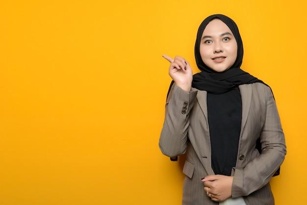アジアの女性の笑顔と空のスペースを指す Premium写真
