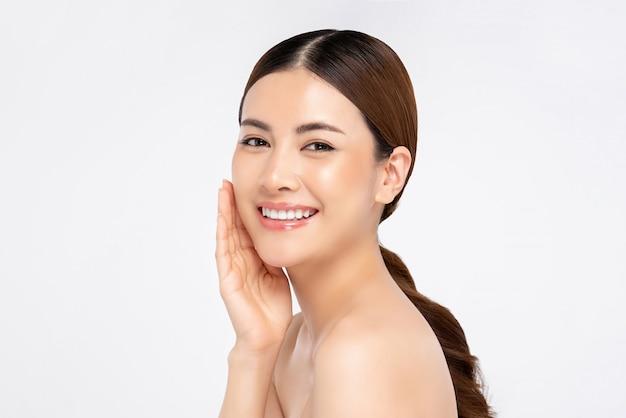 Азиатская женщина улыбается с рукой, касаясь лица для красоты и ухода за кожей концепции Premium Фотографии