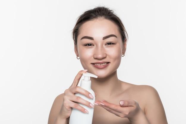 Азиатская женщина сжимает лосьон руки изолированный на белой стене. Бесплатные Фотографии