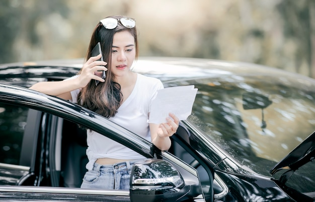 Asian woman standing by broken down car and using smartphone for assistance. Premium Photo