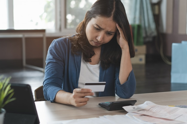 Asian woman stress with credit card debt. Premium Photo