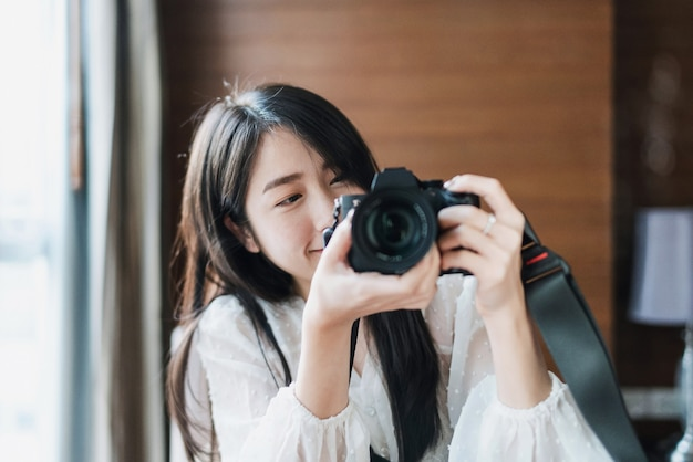 Asian woman taking photo by mirrorless digital camera, with smiling face Premium Photo