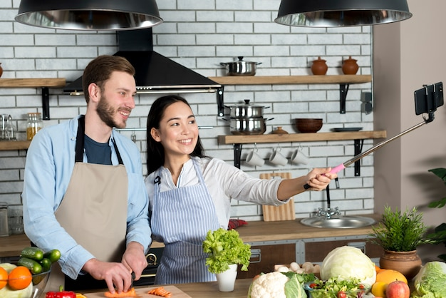 Asian woman taking selfie on mobile phone with her young husband standing behind kitchen counter Free Photo