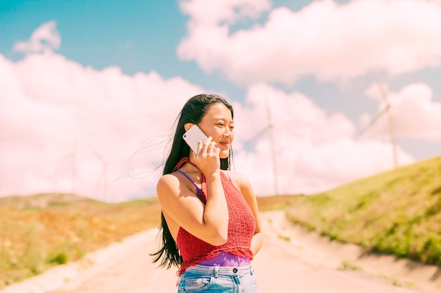 Asian woman talking on phone in countryside Free Photo