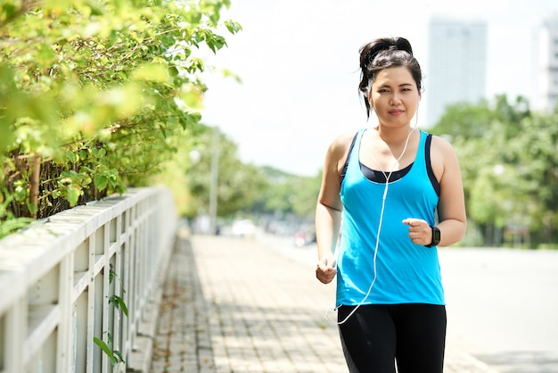 Asian woman in tank top and leggings, with earphones, jogging in morning in urban street Free Photo