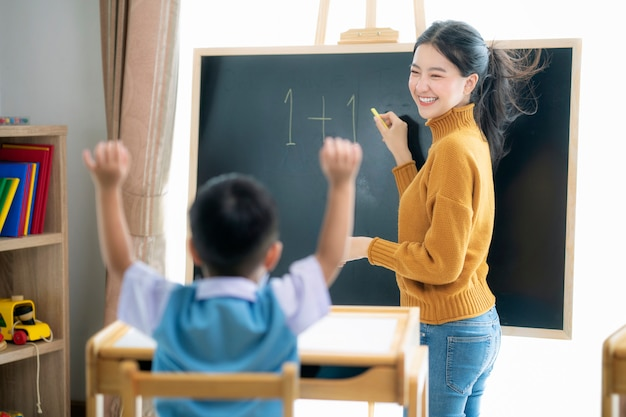 Asian woman teacher and her smart student in class room with backboard background Premium Photo