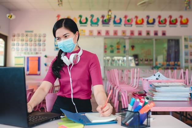 オンライン幼稚園の生徒を教える医療マスクを身に着けているアジアの女性教師教師と生徒はオンラインビデオ会議システムを使用して生徒を教えています。 Premium写真