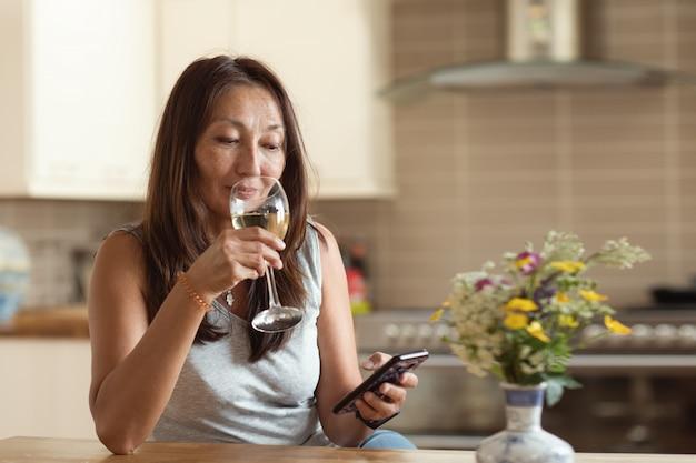 Азиатская женщина текстовых сообщений друзьям по телефону Premium Фотографии