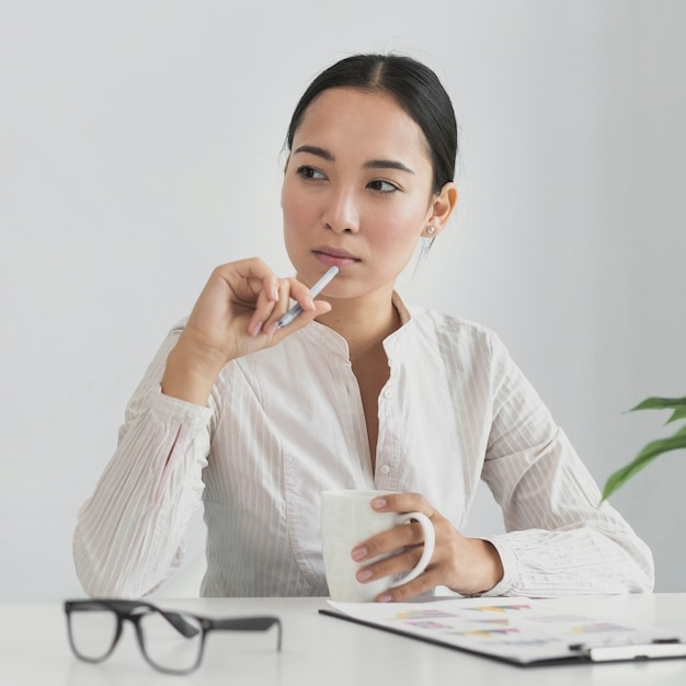 Asian woman thinking in the office Free Photo