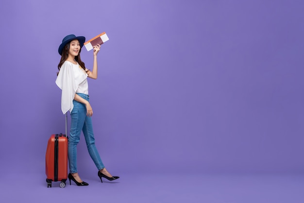 Asian woman tourist with baggage showing passport and boarding pass Premium Photo