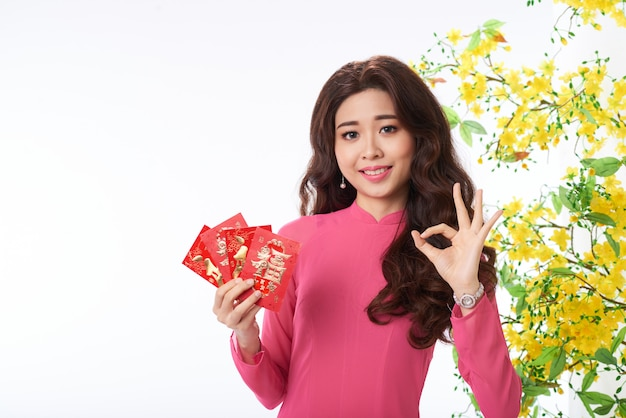 Asian woman in traditional dress gesturing to greet happy holidays Free Photo