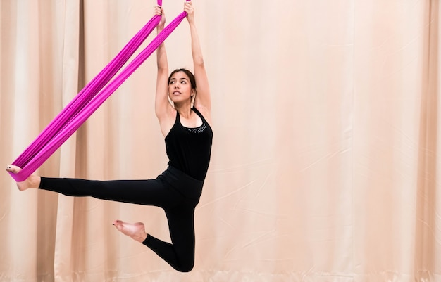Asian woman training in fitness room with fly yoga elements Premium Photo