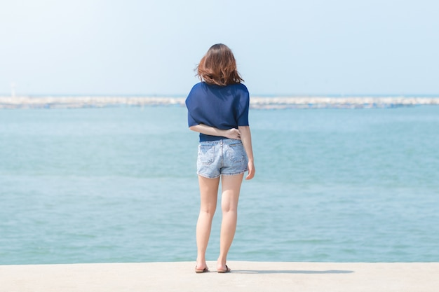 Asian woman traveler standing and looking around the sea. Premium Photo