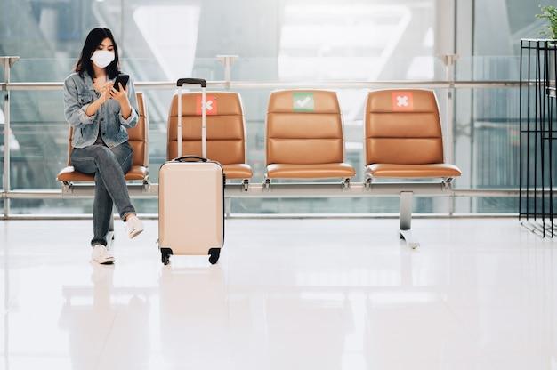 Азиатская женщина-путешественница в маске сидит на стуле социального дистанцирования с багажом, используя смартфон во время вспышки коронавируса или covid-19 Premium Фотографии