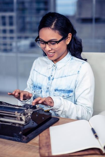 Asian woman typewriting in office Premium Photo