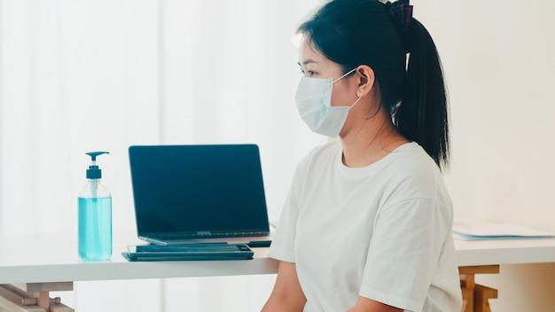 코로나 바이러스를 보호하기 위해 태블릿을 열기 전에 알코올 젤 손 소독제 세척 손을 사용하여 아시아 여자. 사회적 거리가 집에 머무르고 자기 검역 시간에 위생을 위해 청소하는 여성 푸시 알코올 무료 사진