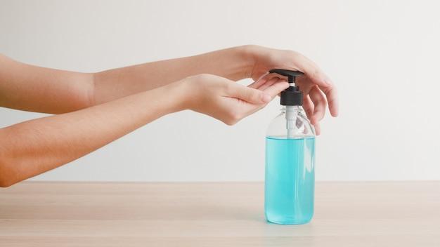 コロナウイルスを保護するためにアルコールゲル手消毒剤洗浄手を使用してアジアの女性。社会的距離が家にいるときや自己検疫時間にいるときは、女性がアルコールボトルを手で清潔にして衛生状態にします。 無料写真