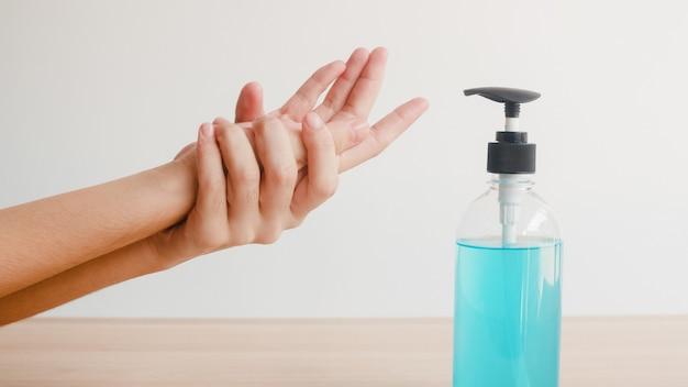 La donna asiatica che usando la mano del lavaggio del disinfettante della mano del gel dell'alcool per protegge il coronavirus. la femmina spinge la bottiglia dell'alcool per pulire la mano per l'igiene quando il distanziamento sociale rimane a casa e il tempo di auto quarantena. Foto Gratuite