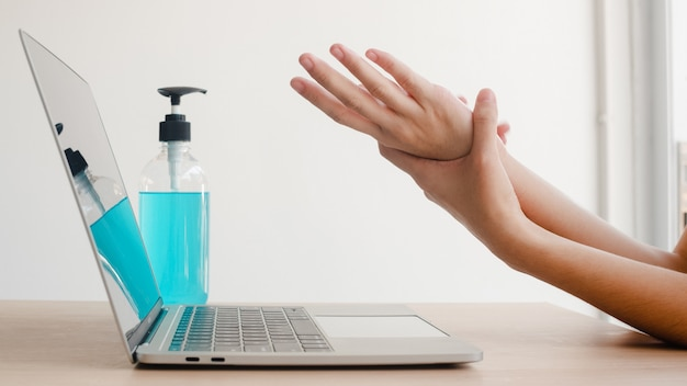 Free Photo | Asian woman using alcohol gel sanitizer wash hand before work on laptop for protect coronavirus. female push alcohol to clean for hygiene when social distancing stay at home and