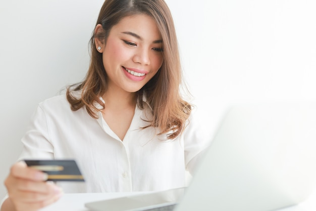 Asian woman using credit card shopping online with laptop computer, Premium Photo