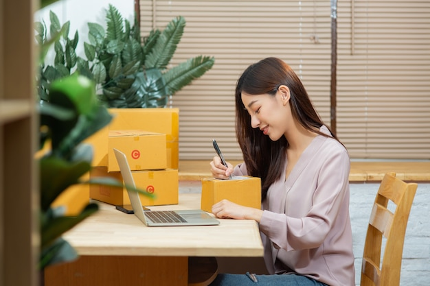Premium Photo | Asian woman using laptop writing on package box working at  home office for online marketing small business owner