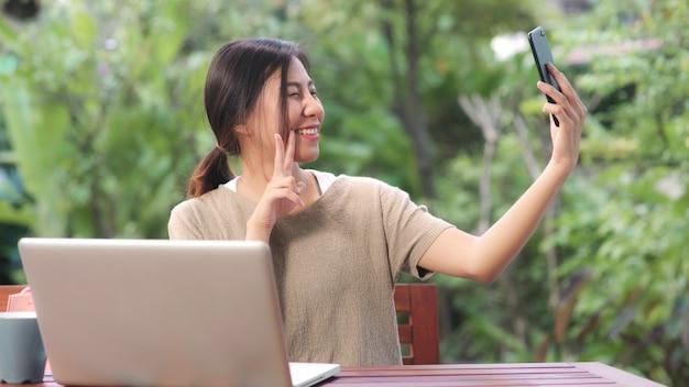 La donna asiatica che utilizza la posta del selfie del telefono cellulare nei media sociali, femmina si rilassa sentendo i sacchetti della spesa di mostra felici che si siedono sulla tavola nel giardino nella mattina. Foto Gratuite