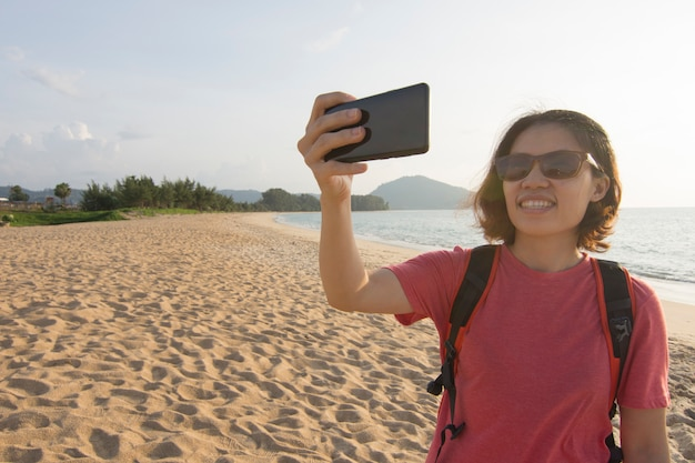 Asian woman using mobile phone on travel vacation at ocean. Premium Photo
