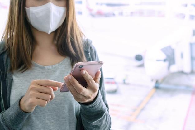 Азиатская женщина с помощью смартфона и хирургической маски в аэропорту. концепция здравоохранения Premium Фотографии
