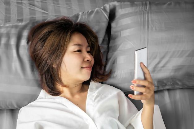 Asian woman using smart phone in bed Premium Photo