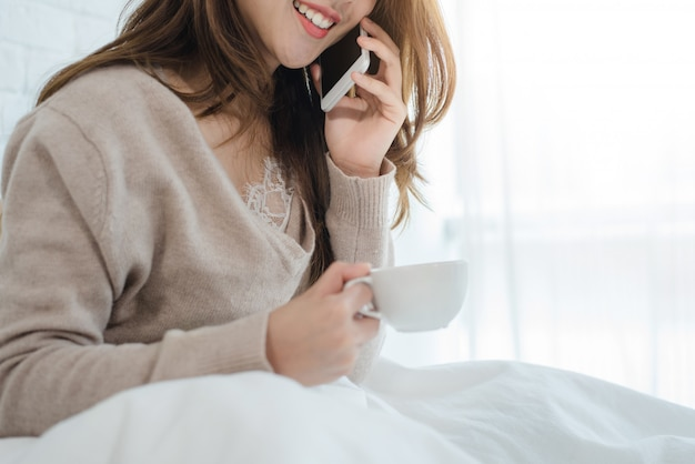 Asian woman using the smartphone on her bed while holding cup of coffee in the morning Free Photo